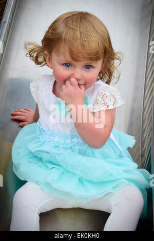 A small, blond child shyly poses on a slide at a playground - Stock Photo