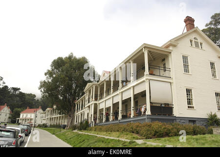 White sky sunny oblique view, to Post HQ Building, people at veranda tables Murray Circle Restaurant, Fort Baker, - Stock Photo