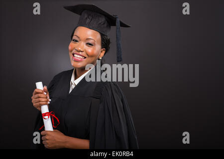 studio portrait of African college graduate on black background - Stock Photo