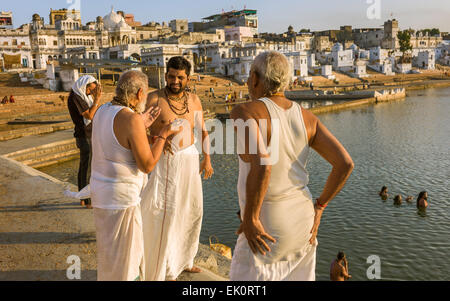 Hindu pilgrims take a ritual bath and offer prayers at the holy lake surrounded by temples - Stock Photo