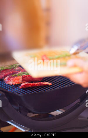 Man hands with fresh meat preparing on grill close up - Stock Photo