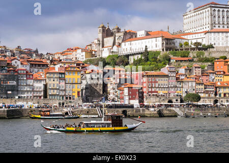 PORTO PORTUGAL RIVER DOURO TOURISTS ON SIGHTSEEING BOAT WITH THE SE CATHEDRAL TOWERS ON THE FAR BANK - Stock Photo