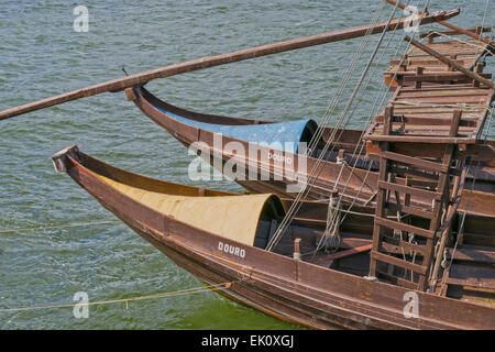 PORTO PORTUGAL RIVER DOURO WOODEN PORT WINE BOATS MOORED ON THE BANKS OF THE RIVER AND LOADED WITH PORT WINE BARRELS - Stock Photo