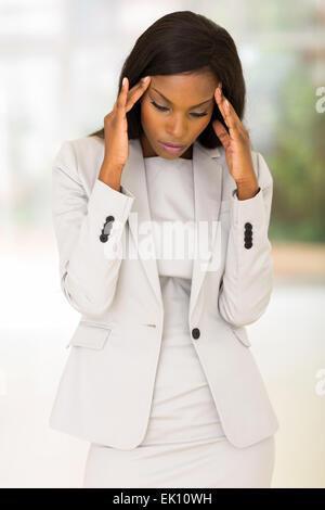 sad African American businesswoman having headache at work - Stock Photo
