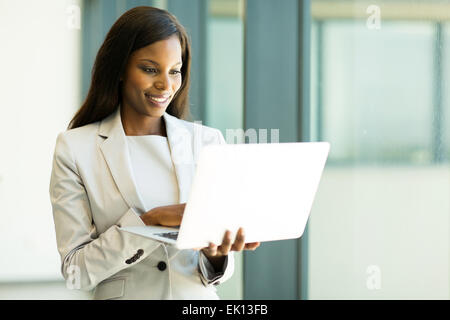 beautiful African businesswoman reading email on her laptop - Stock Photo