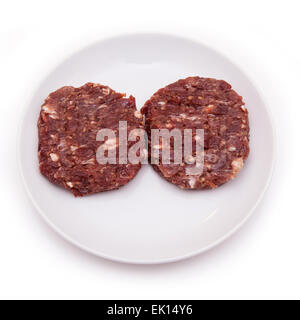 Kangaroo meat burgers uncooked isolated on a white studio background. - Stock Photo
