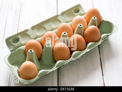 Nine fresh chicken eggs in green egg-box on white painted wooden background - Stock Photo