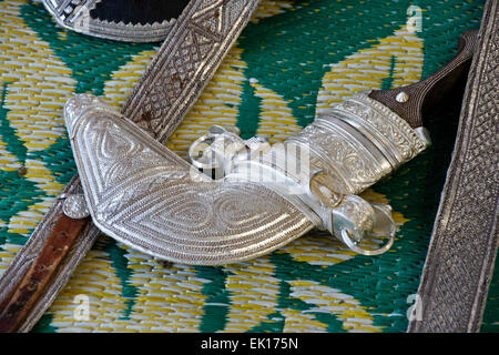 Engraved silver belts and khanjar (dagger) for sale in market, Sinaw, Oman - Stock Photo