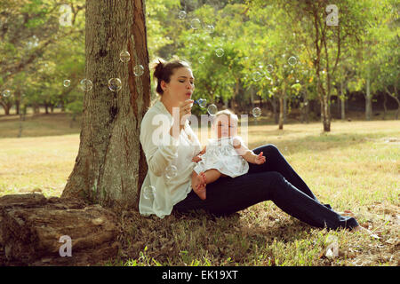 Beautiful woman sitting down tree in park and leaning on trunk with her little baby on legs, playing with her daughter - Stock Photo