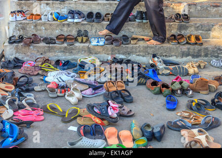 A man looking for his shoes outside a temple in Ayutthaya - Stock Photo