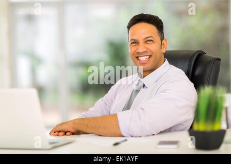 portrait of mid age business man sitting in modern office - Stock Photo