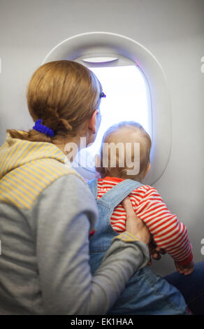 Mother and baby son looking out of window while on board of airplane - Stock Photo