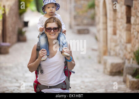 Young Caucasian woman tourist carrying her little son on shoulders - Stock Photo