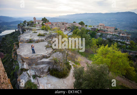 Young couple standing on cliff and enjoying valley view of old village Siurana - Stock Photo