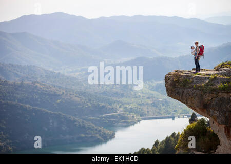 Young mother with baby in sling standing on cliff and enjoying valley view - Stock Photo