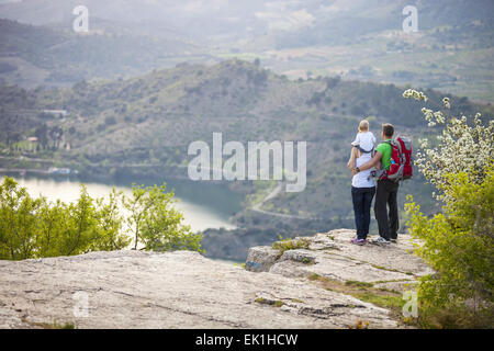Young couple with toddler boy standing on cliff and enjoying view below - Stock Photo