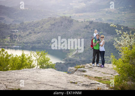 Young couple with toddler boy standing on cliff and smiling - Stock Photo