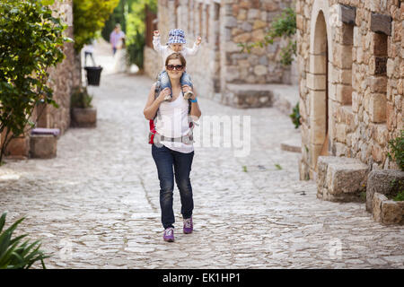 Young Caucasian woman tourist carrying her little son on shoulders while exploring old Spanish town - Stock Photo