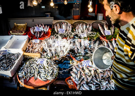 man throwing water over fish in fish booth - Stock Photo