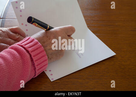 Close up Elderly woman using fountain pen to write greetings on birthday card - Stock Photo