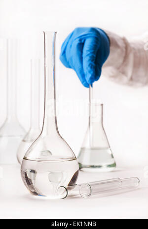 assistant mix reagents into the flask on a white background - Stock Photo