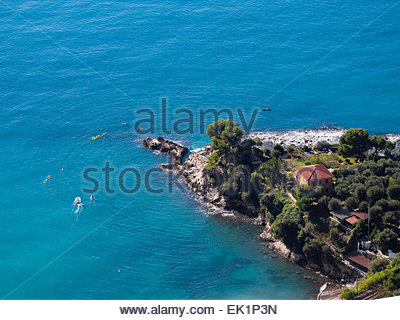 Aerial view of small stretch of Italian rocky coast with small boats and canoes on calm blue sea in sunny autumn - Stock Photo