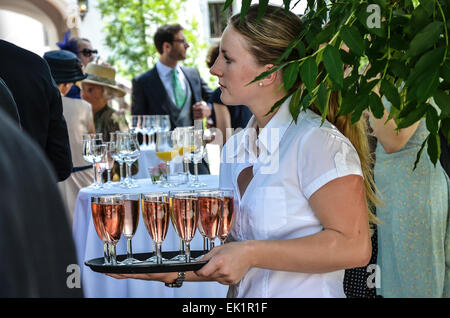 wedding after ceremony party outdoors wedding guests  wedding dress colourful hats  eating drinking talking - Stock Photo