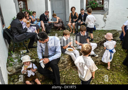 wedding after ceremony party outdoors wedding guests  wedding dress colourful hats  eating drinking talking families - Stock Photo