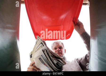 Man dropping newspaper into household waste recycling bin - Stock Photo