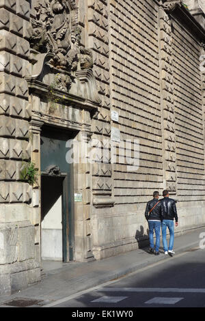 Two young men walking past entrance to Church of Bethlehem on Rambla dels Estudis, Barcelona, Catalonia, Spain - Stock Photo