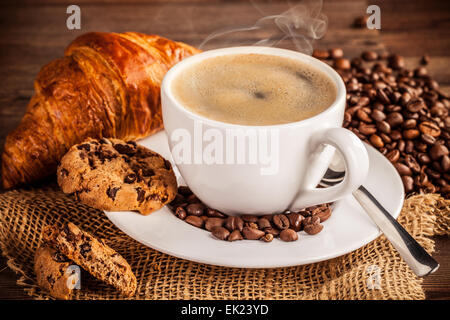 Coffee still life with porcelain cup served on wooden table - Stock Photo