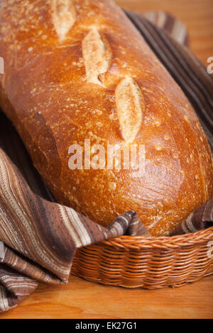 Loaf of homemade sourdough bread in a bread basket lined with a brown striped tea towel - Stock Photo