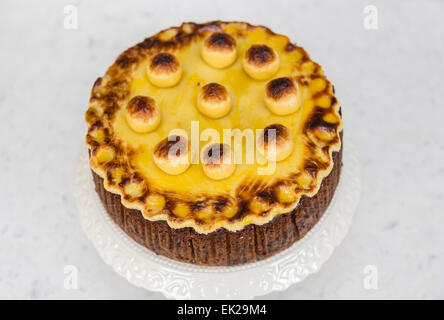 Traditional home baked simnel cake on a white china cake stand for Easter - fruit cake with toasted marzipan topping - Stock Photo