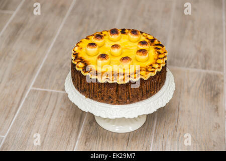 Traditional round home baked simnel cake on a white china cake stand for Easter - fruit cake with toasted marzipan topping and balls