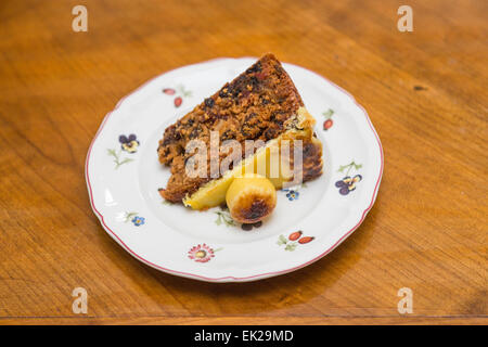 Slice of traditional Easter simnel cake, a fruit cale with marzipan topping and ball served on a flowery white china - Stock Photo