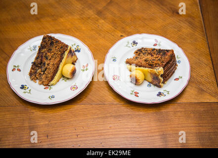 Two slices of traditional Easter simnel cake, a fruit cake with marzipan topping and balls served on flowery white - Stock Photo
