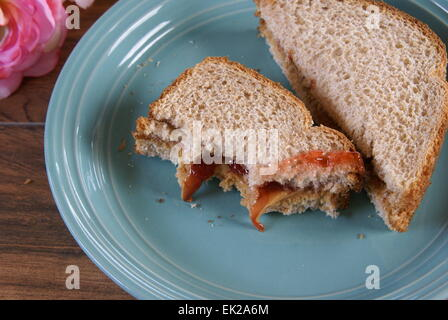 Partially eaten sandwich made of wheat bread, smooth peanut butter and strawberry preserves. - Stock Photo