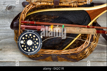 Antique fly fishing reel, rod, flies, and net on top of open creel with rustic wood underneath. Layout in horizontal - Stock Photo