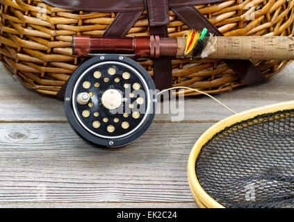 antique fly fishing reel, rod, landing net, creel and artificial flies on rustic wood. Layout in horizontal format. - Stock Photo