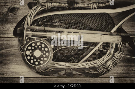 Vintage and aging grain concept of an antique fly fishing reel, rod, flies, and net on top of open creel with rustic - Stock Photo