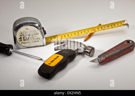 Assorted Tools on a white work surface - Stock Photo