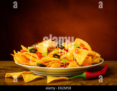 still life with baked nachos, cheese, olives and chili peppers - Stock Photo