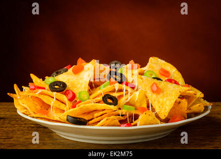 nachos tortilla chips with cheese, olives and chili peppers on a plate - Stock Photo