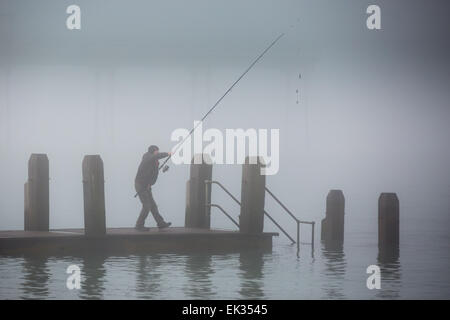 Aberystwyth, Wales, UK. 6 April 2015.  Easter Monday. Weather. A fisherman preparing to cast from a wooden jetty - Stock Photo