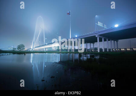 Wide long exposure shot of Margaret Hunt Hill Bridge in downtown Dallas Texas on a misty foggy night with a reflection. - Stock Photo