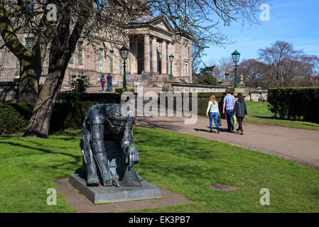 Visitors walking by the figure of Sir Isaac Newton by Sir Eduardo Paolozzi at the entrance to the Gallery of Modern - Stock Photo