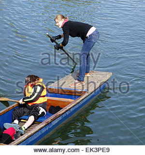 Young woman balancing when punting on the River Cam in Cambridge in the spring sunshine - Stock Photo