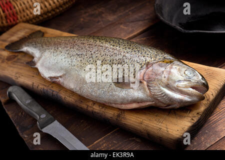 A rainbow trout on cutting board in a rustic cabin. - Stock Photo