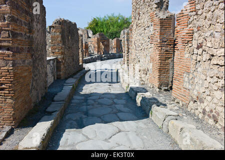 Roman ruins in Pompei, Italy. Wheel ruts and ruined buildings in the cobbled street of Via Consolare - Stock Photo