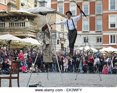 A tightrope walker entertaining a crowd in Covent Garden London UK - Stock Photo